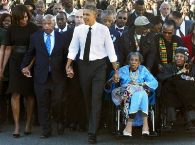 """In this March 7, 2015 file photo, President Barack Obama, center, holds hands with Rep. John Lewis, D-Ga., left, and Amelia Boynton Robinson, right, who were both beaten during """"Bloody Sunday,"""" as they walk across the Edmund Pettus Bridge in Selma, Ala., for the 50th anniversary of """"Bloody Sunday."""" Boynton Robinson, a civil rights activist who nearly died while helping lead the Selma march on """"Bloody Sunday,"""" championed voting rights for blacks, and was the first black woman to run for Congress in Alabama, died Wednesday, Aug. 26, 2015. She was 104. Boynton Robinson was hospitalized in July after having a major stroke and turned 104 on Aug. 18. (AP Photo/Jacquelyn Martin, File)"""