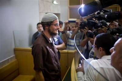 """Head of a Jewish extremist group Meir Ettinger appears in court in Nazareth Illit , Israel, Tuesday, Aug. 4, 2015. Israel said Tuesday it was interrogating the suspected head of a Jewish extremist group in the first arrest of an Israeli suspect following last week's arson attack in the West Bank that killed a Palestinian toddler and wounded his brother and parents. According to the Shin Bet security agency, 23-year-old Ettinger was arrested late Monday for """"involvement in an extremist Jewish organization."""" (AP Photo/Ariel Schalit)"""