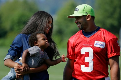 Seattle Seahawks quarterback Russell Wilson, right, walks with his girlfriend, entertainer Ciara Harris, and Harris' son Future, 1, Thursday, Aug. 13, 2015, following NFL football training camp in Renton, Wash. (AP Photo/Ted S. Warren)