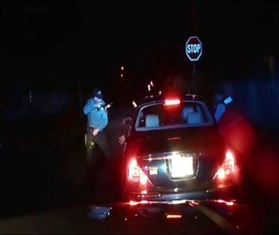 In this frame grab from an officer's dashboard camera taken Dec. 30, 2014, and provided by the Bridgeton, N..J. Police Department, police officers Braheme Days and Roger Worley stand near a car they pulled over for running a stop sign in Bridgeton. A grand jury has voted not to file charges against the two police officers for fatally shooting a man who defied orders by stepping out of a car with his hands raised during a traffic stop, a killing captured by their patrol car's dashboard camera, prosecutors said Thursday, Aug. 20, 2015. (AP Photo/Bridgeton Police Department, File)