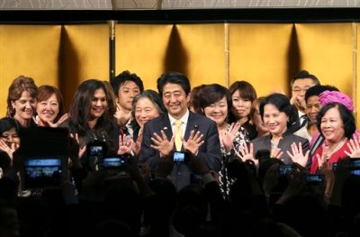 Japanese Prime Minister Shinzo Abe, center, poses for a photo with participants during a reception of WAW!, or the World Assembly for Women, in Tokyo, Friday, Aug. 28, 2015. More than 100 people from about 40 countries participated in the open forum for women. Japanese lawmakers approved a law Friday requiring large employers to set and publicize targets for hiring or promoting women as managers. The law approved by a vote of 230-1 in the House of Councillors is intended to promote greater gender equality and counter labor shortages that are arising as Japan's population ages and declines. The decision coincided with the international conference showcasing Abe's commitment to increasing the share of women in leadership positions to 30 percent. (AP Photo/Koji Sasahara, Pool)