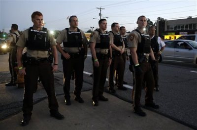 Police patrol on Monday, Aug. 10, 2015, in Ferguson, Mo. Ferguson was a community on edge again Monday, a day after a protest marking the anniversary of Michael Brown's death was punctuated with gunshots. (AP Photo/Jeff Roberson)