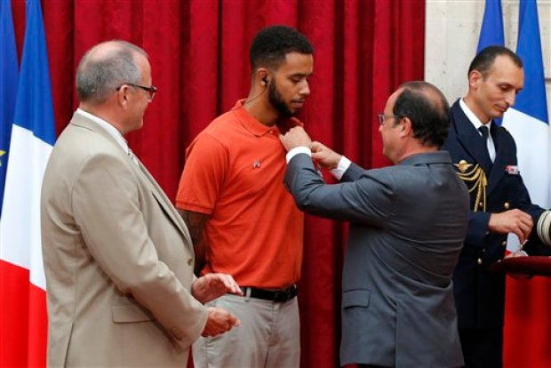 French President Francois Hollande, right, awards with the Legion of Honor Anthony Sadler, a senior at Sacramento University in California as British businessman Chris Norman, left, looks on at the Elysee Palace, Monday Aug.24, 2015 in Paris, France. Hollande  pinned the Legion of Honor medal on U.S. Airman Spencer Stone, National Guardsman Alek Skarlatos, and their years-long friend Anthony Sadler, who subdued the gunman as he moved through the train with an assault rifle strapped to his bare chest. The British businessman, Chris Norman, also jumped into the fray. (AP Photo/Michel Euler, Pool)
