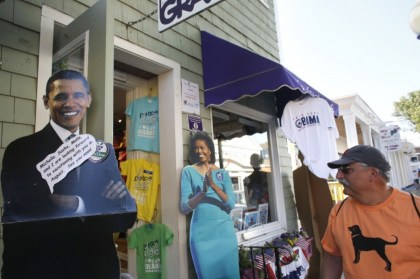 A passer-by, right, walks past a storefront that features cut-outs of President Barack Obama, left, and first lady Michelle Obama, center, Saturday, Aug. 9, 2014, in Oak Bluffs, Mass., on the island of Martha's Vineyard. (AP Photo/Steven Senne)