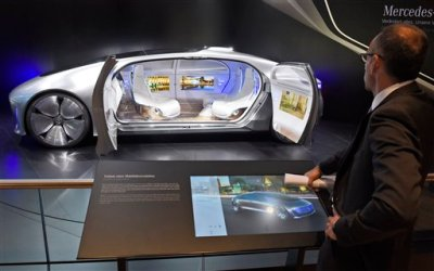 A visitor looks at the 'F 015 Luxury in Motion' autonomous driving vehicle at the Mercedes stand on the first press day of the Frankfurt Auto Show IAA in Frankfurt, Germany, Tuesday, Sept. 15, 2015. The car show runs through Sept. 27. (AP Photo/Jens Meyer)