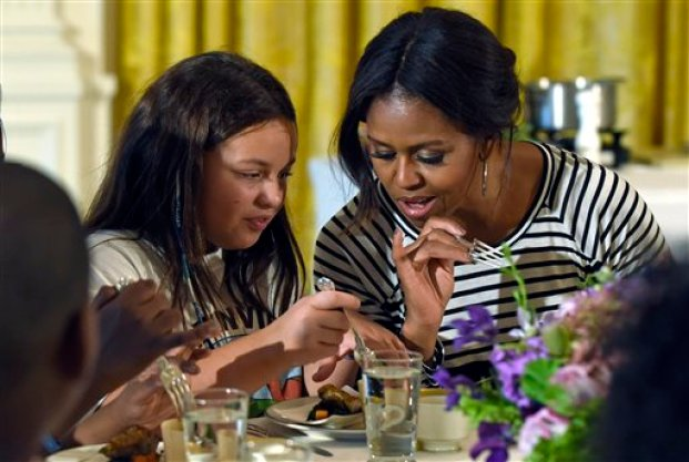 "In this Oct. 14, 2014 file photo, first lady Michelle Obama and a student look over their plates as they eat lunch in the East Room of the White House in Washington following the annual fall harvest of the White House Kitchen Garden. Congress will have to decide soon whether it wants another food fight with first lady Michelle Obama and the administration over what's served in the school lunch line. School food rules pitted Republicans seeking full exemptions for some schools against Obama in 2014, with the first lady declaring she'd fight ""to the bitter end"" to make sure kids have good nutrition.(AP Photo/Susan Walsh, File)"