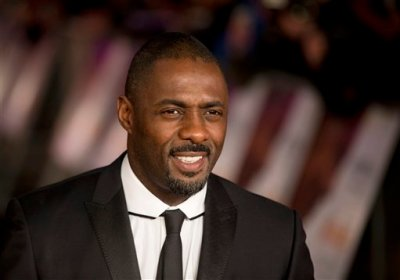 """FILE - In this file photo photo dated Thursday, Dec. 5, 2013, British actor Idris Elba who plays Nelson Mandela in the movie """"Mandela: Long Walk to Freedom"""", poses for photographers in London. The author of the new James Bond novel Anthony Horowitz, apologized on Tuesday Sept. 1, 2015, after he said that British actor Idris Elba is """"too street"""" to play the iconic British James Bond 007 character, during a newspaper interview published last weekend. (AP Photo/Matt Dunham, FILE)"""