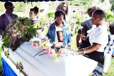 Family and friends leave roses on the casket of 9-year-old Jamyla Bolden at Laural Hill Memorial Gardens Cemetery Saturday afternoon. (Wiley Price/St. Louis American)