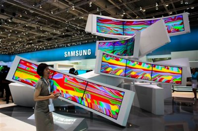 This is a Friday, Sept. 5, 2014 file photo of a woman as she passes an installation with curved screens, displayed by Samsung at the consumer electronic fair IFA in Berlin, Germany. Europe's flagship gadget show, the IFA in Berlin, opens its doors to the public on Friday Sept. 4, 2015 . Almost 1,500 companies and over 250 000 people are expected to visit the event, which runs through Sept. 9. (AP Photo/Markus Schreiber)