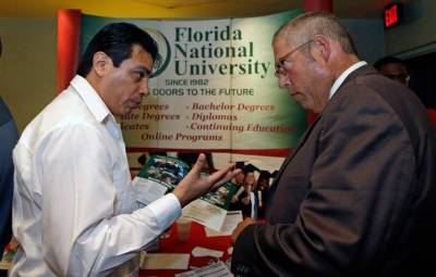 Luigi Valdivieso, left, talks about job opportunities to Richard Solano at a job fair in Miami Lakes, on July 15, 2015. A new report says Florida is one of the worst state's in the nation when it comes to paying unemployment benefits. (Alan Diaz/AP Photo)