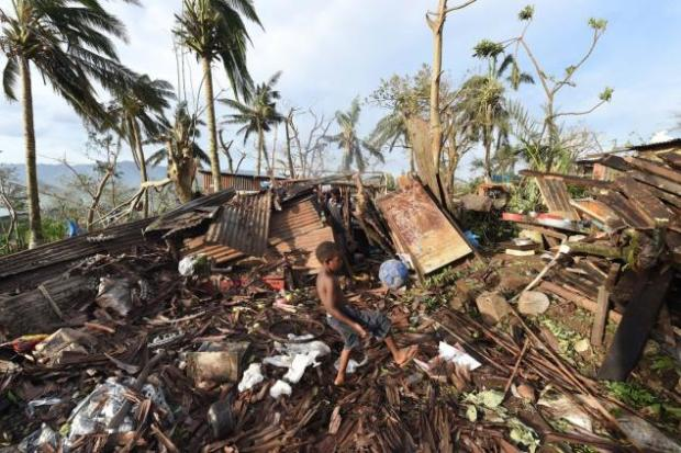 A boy kicks a ball through the ruins of his family home as his father, Phillip, at back, picks through  debris in Port Vila, Vanuatu, on Monday. (Dave Hunt/AP Photo)