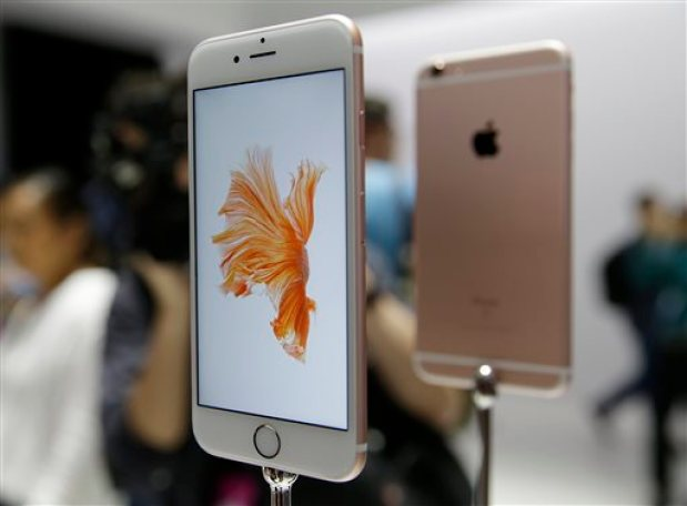In this Sept. 9, 2015 photo, people look over the new Apple iPhone 6s models during a product display following an Apple event in San Francisco. Photography gets even better with Apple's new iPhones, making them worth getting for $100 more than last year's models.(AP Photo/Eric Risberg)
