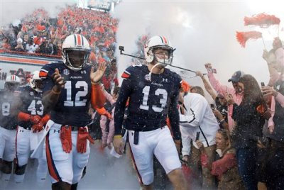In this Oct. 4, 2014, file photo, Auburn quarterbacks Jonathan Wallace (12) and Sean White (13) run out onto the field for an NCAA college football game against LSU in Auburn, Ala. Johnson, the media's pick as the preseason second-team all-SEC quarterback, has been benched after throwing six interceptions in the Tigers' first three games. Redshirt freshman Sean White, who hasn't taken a snap in a college game, starts Saturday against Mississippi State. (AP Photo/Brynn Anderson, File)