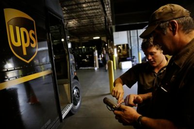 In this June 20, 2014 photo, United Parcel Service driver Richard Trzcinski, right, goes over ORION, the automated computer system that devises optimal routes for its drivers, with fellow driver Daniel Petranck before heading out on deliveries from the company's sorting facility in Roswell, Ga. UPS on Tuesday, Sept. 15, 2015 said it will hire 90,000 to 95,000 employees — about the same as last year — to help handle shipping and deliveries over the holiday season. (AP Photo/David Goldman, File)