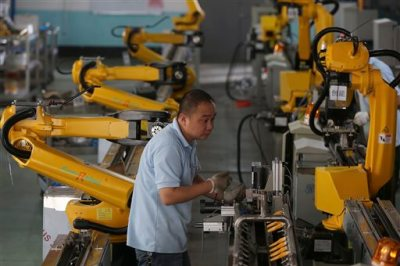 In this Aug. 25, 2015 photo, a worker tests robots' arms at a manufacture factory in Jiaxing in east China's Zhejiang province. For decades, China's manufacturers employed waves of young migrant workers from the countryside to work at countless factories in coastal provinces, churning out cheap toys, clothing and electronics. Now, factories are rapidly replacing those workers with automation, a pivot that's encouraged by rising wages and new official directives aimed at helping the country move away from low-cost manufacturing. (Chinatopix via AP)