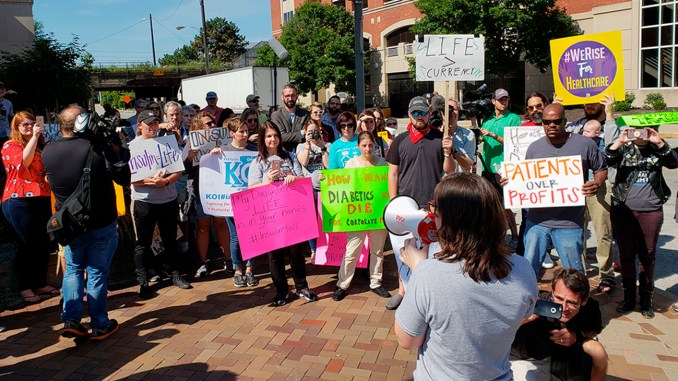 Elizabeth Pfiester, founder of T1International, addresses a crowd outside the Indianapolis headquarters of pharmaceutical giant Eli Lilly and Co. in September. (Bram Sable-Smith/NPR)