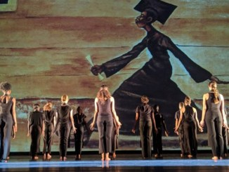 """Dancers strike a pose as Ernie Banks' painting """"The Graduate"""" looms in the background during TU Dance's 15th anniversary concert."""