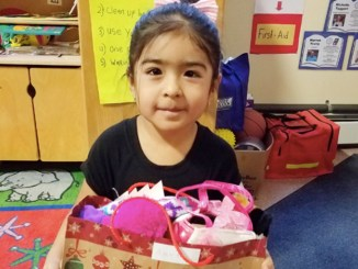 Head Start student Amaia Mendez, 3, of Middletown with her gift bag at Head Start in Scotchtown.