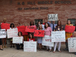 Wearing red, teachers at H.G. Hill Middle School pose with signs May 1, 2019. They want a raise six times more than the 3% Mayor David Briley has offered.