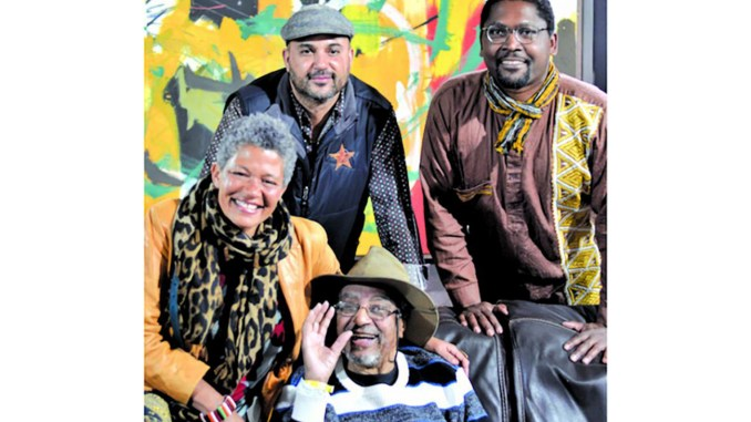 Artist Arthur Monroe sits below his son and exhibit organizer Alistair Monroe with Winona Lewis, left, and Alpha Lewis. Photo by Sara Herrera.