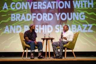 Rashid Shabazz and Bradford Young sit on stage at BlackStar Film Festival in front of a large screen.