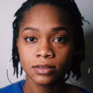 A headshot for Tshay Williams, a Black person weaing a blue shirt and large hoop earrings.