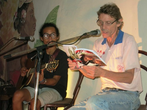 a guitarist and a reader onstage