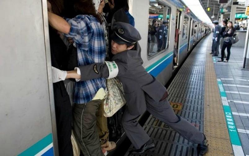 oshiya sedang memastikan penumpang kereta masuk sepenuhnya ke gerbong