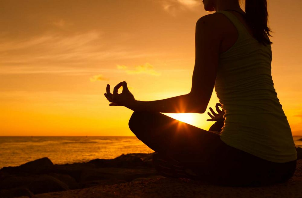 gadis meditasi seorang diri di tepi pantai