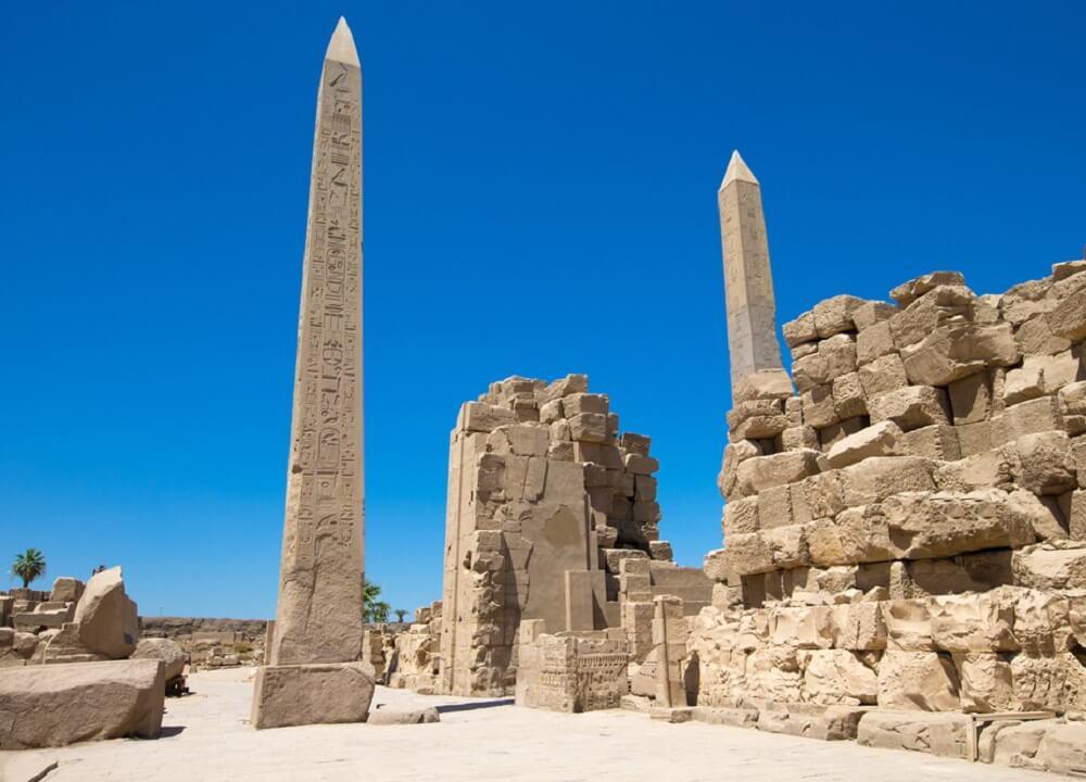 obelisk mesir menjulang di sekitar reruntuhan kuil kuno