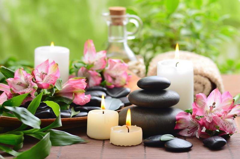 lilin dan botol aromaterapi terletak di atas meja