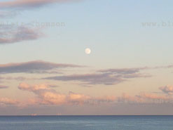 distant image, full moon small above clouds and sea horizon