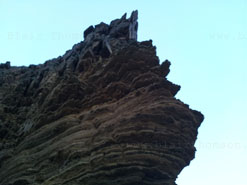 jagged brown rockface, sandy and eroded, summer night sky above