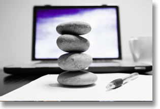 Zen rocks on an office desk with a laptop, pen, and paper