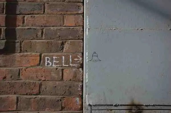"Photo of a door with ""bell"" written in chalk and an arrow pointing to a empty space on the door."