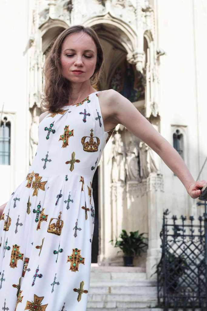 Weißes Kleid mit Kreuzmotiv im Hintergrund eine Kirche