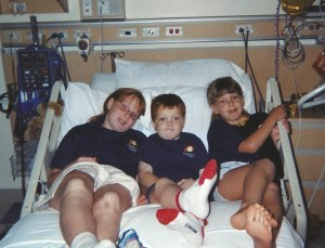 Siblings snuggle on the hospital bed.