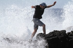 Pedro runs from the crashing waves at South Point, HI