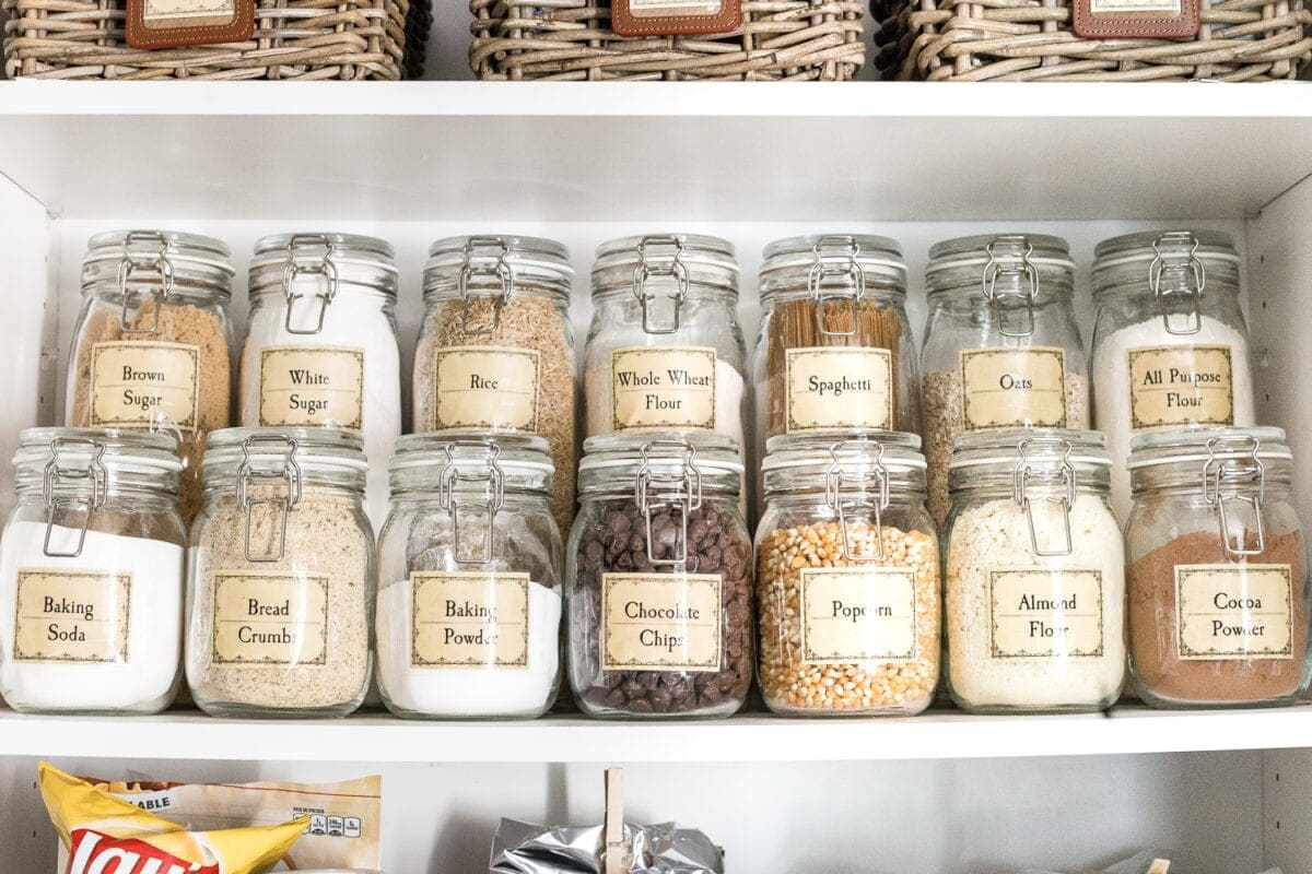 clear canisters and baskets in a pantry cabinet