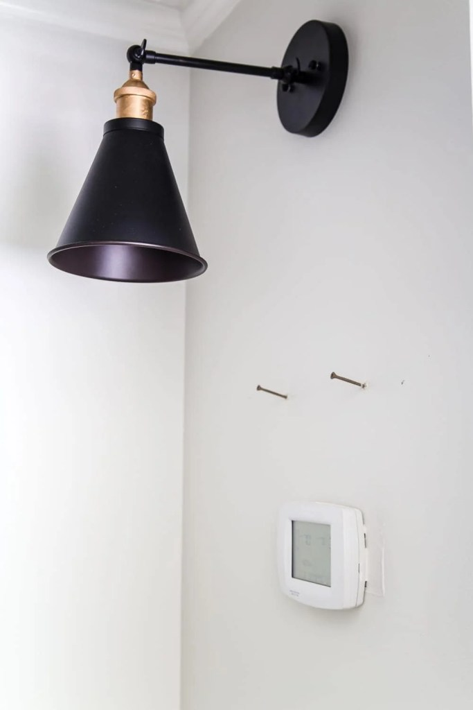 Simple Thermostat Cover and Hallway Progress | A dark, beige hallway gets a light and bright makeover, plus a solution for creating an inexpensive thermostat cover and sconce lighting without the electrical work. #thermostatcover #hallway #hallwaymakeover #beforeandafter #sconce #sconcelight #walldecor #wallart #budgetdecor #freeart #decortrick #eyesorecover Easy Thermostat Cover