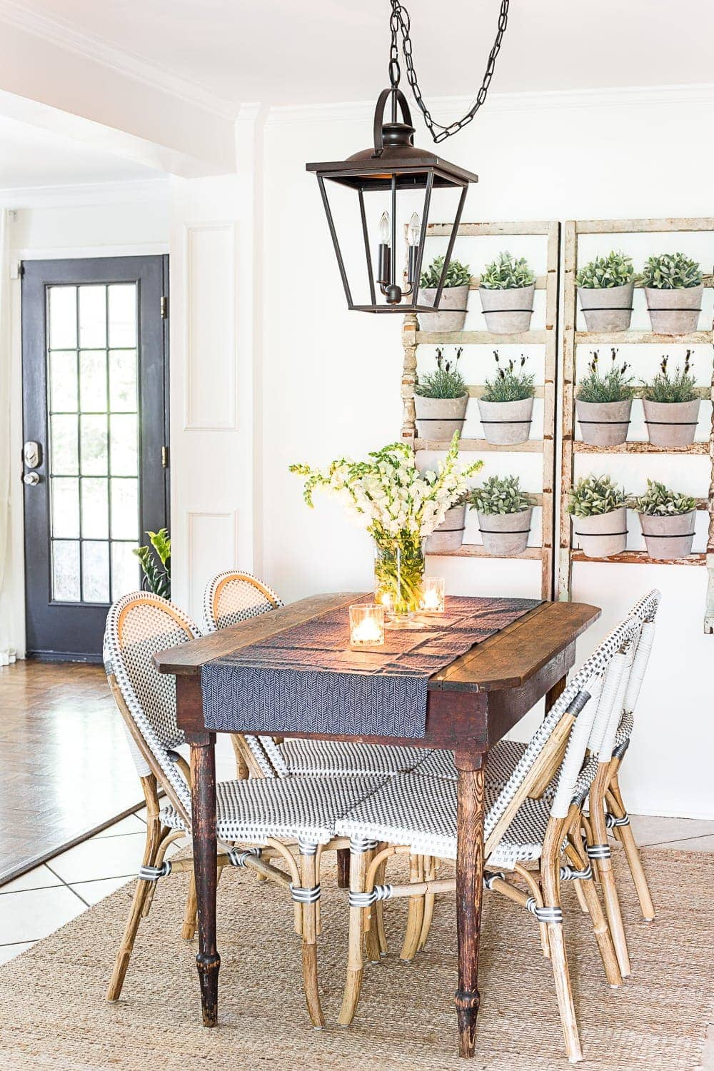 breakfast nook decorated for summer with a DIY wall planter made from antique banisters