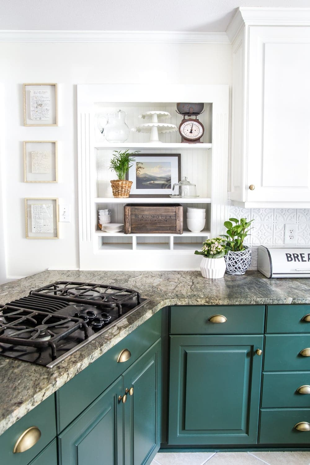 Kitchen shelves with dark green cabinets and framed handwritten recipes for art