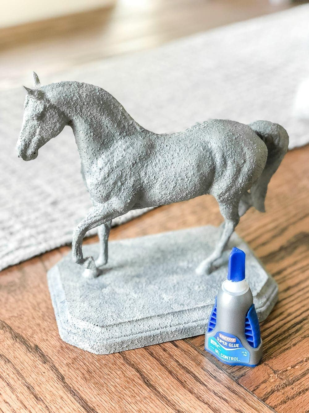 How to turn a toy horse figurine into a designer-inspired concrete equestrian statuette using just paint, wood craft, and glue. #thriftymakeover