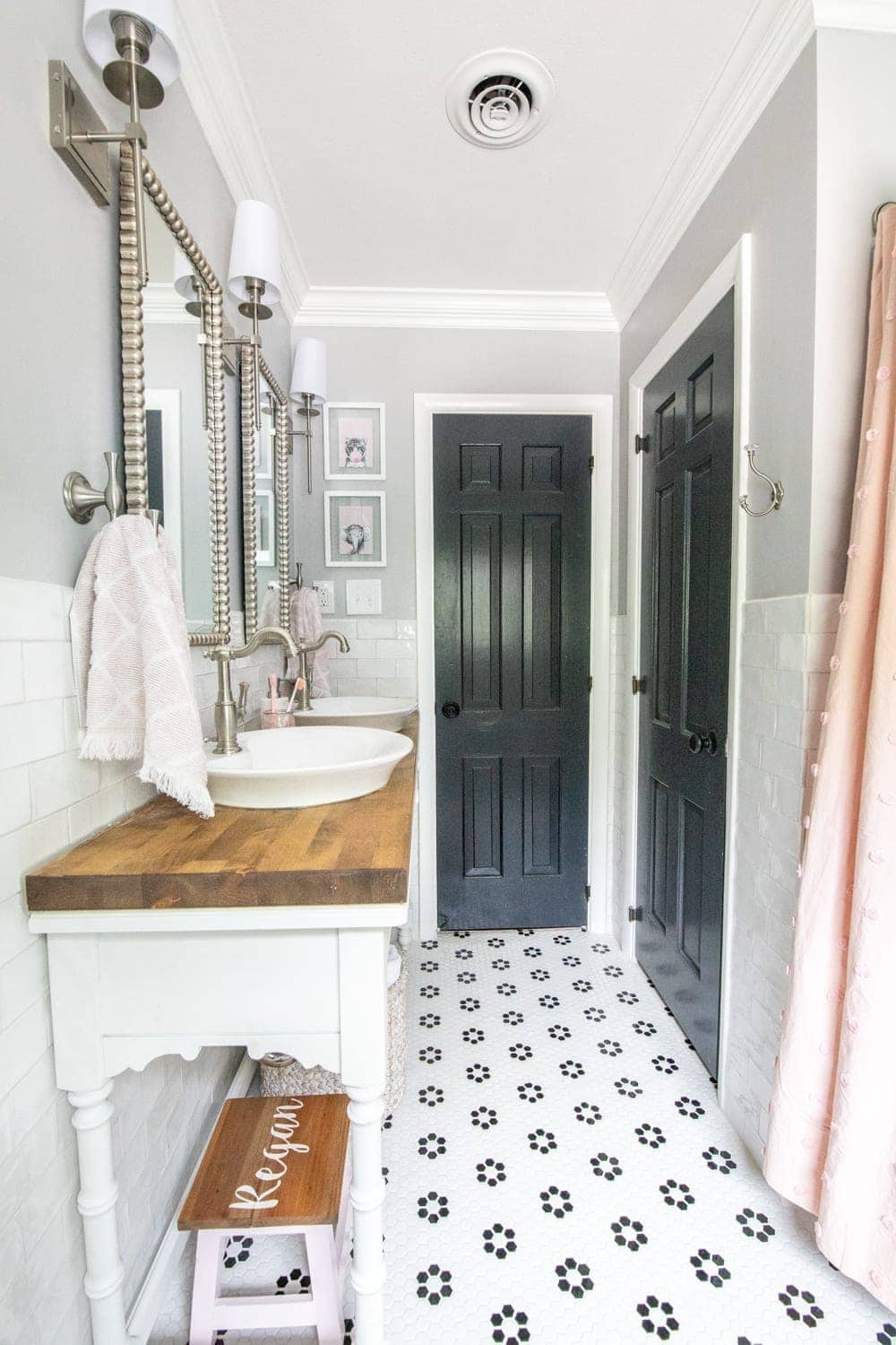 Girls' Bathroom Decor Details & Sources | Console table converted into a vanity with vessel sinks and retro flower floor tile | Benjamin Moore Stonington Gray walls and Benjamin Moore Wrought Iron doors