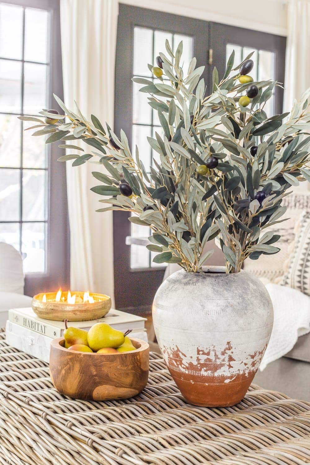 terracotta vase with olive branches wooden bowl with pears and fall candle
