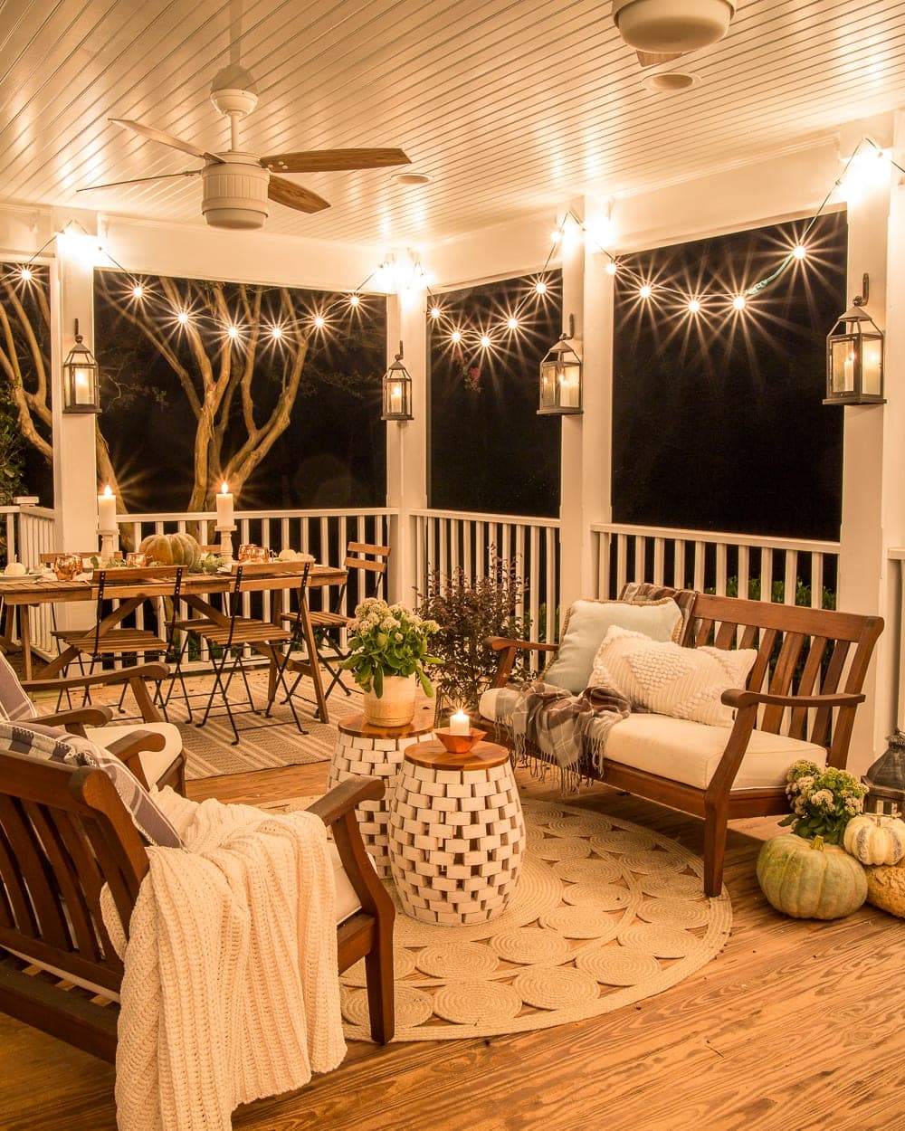 back porch decorated for fall with string lights