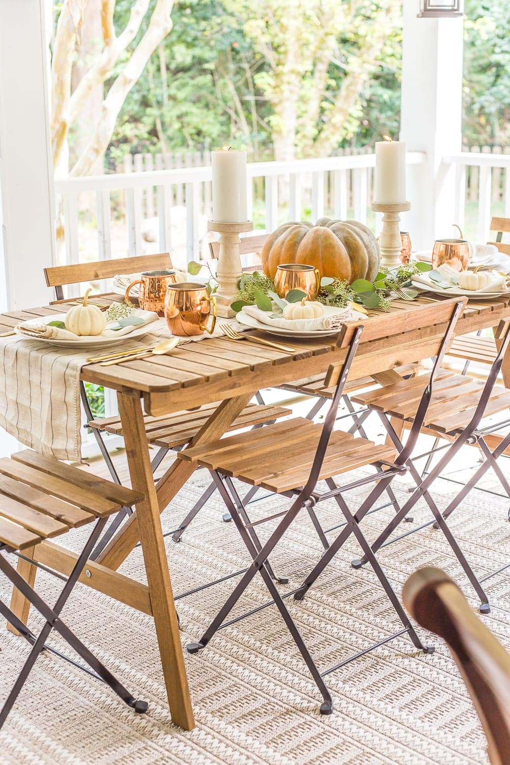 outdoor dining table decorated for fall with pumpkin centerpiece, eucalyptus, and copper