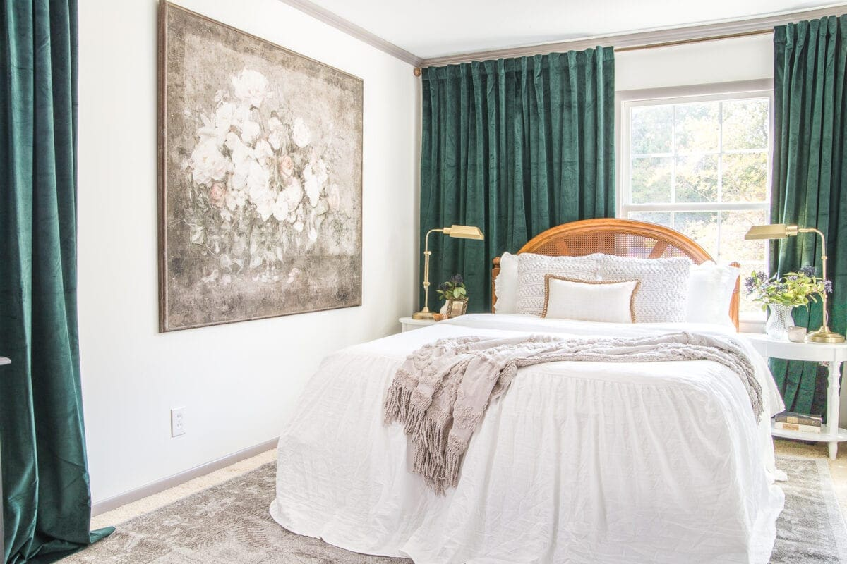 guest bedroom with green velvet curtains and off centered window trick