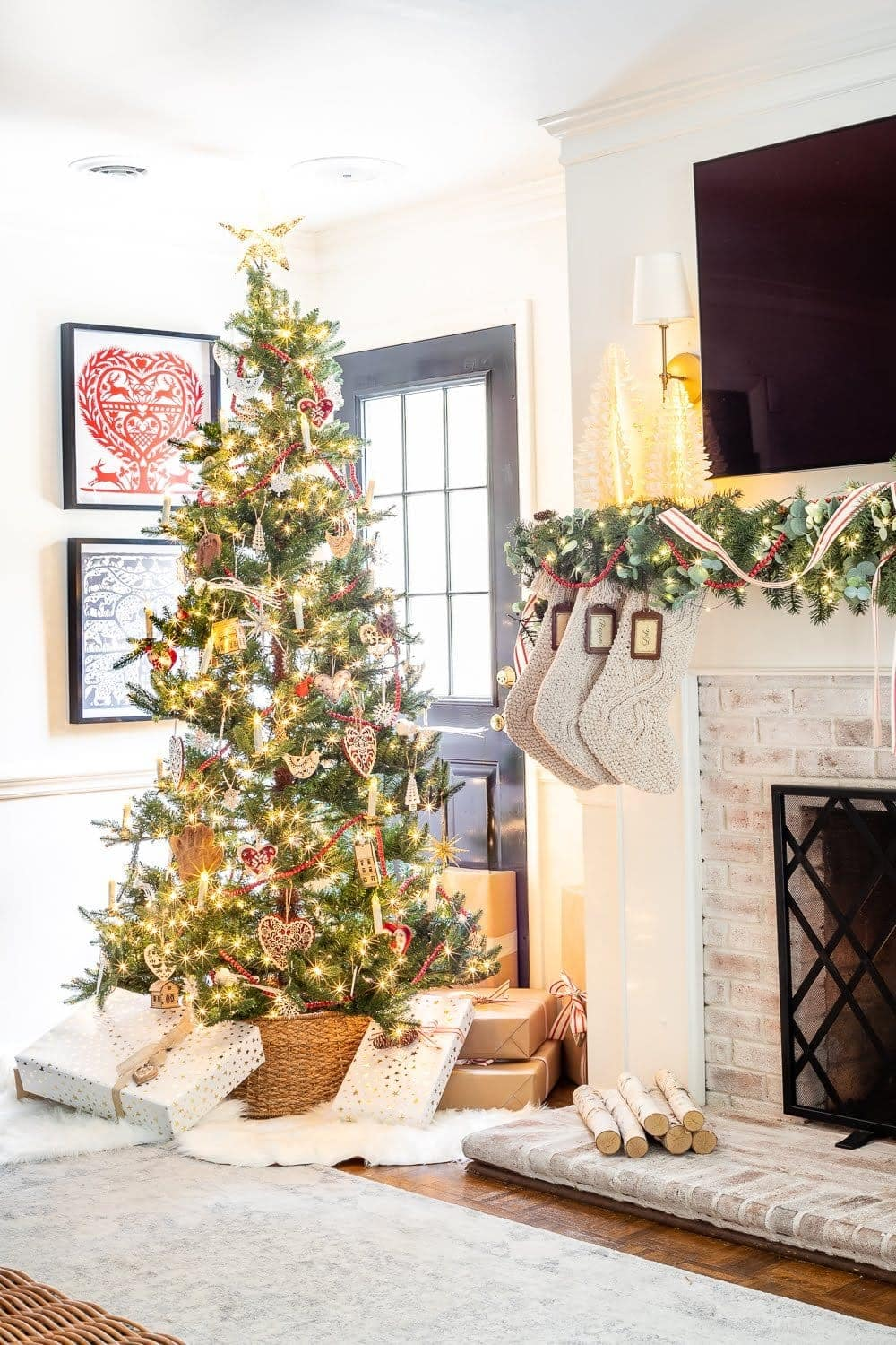 Swedish Christmas tree with Scandinavian inspired ornaments, abundant greenery, chunky knit stockings, nature touches, and pops of red.