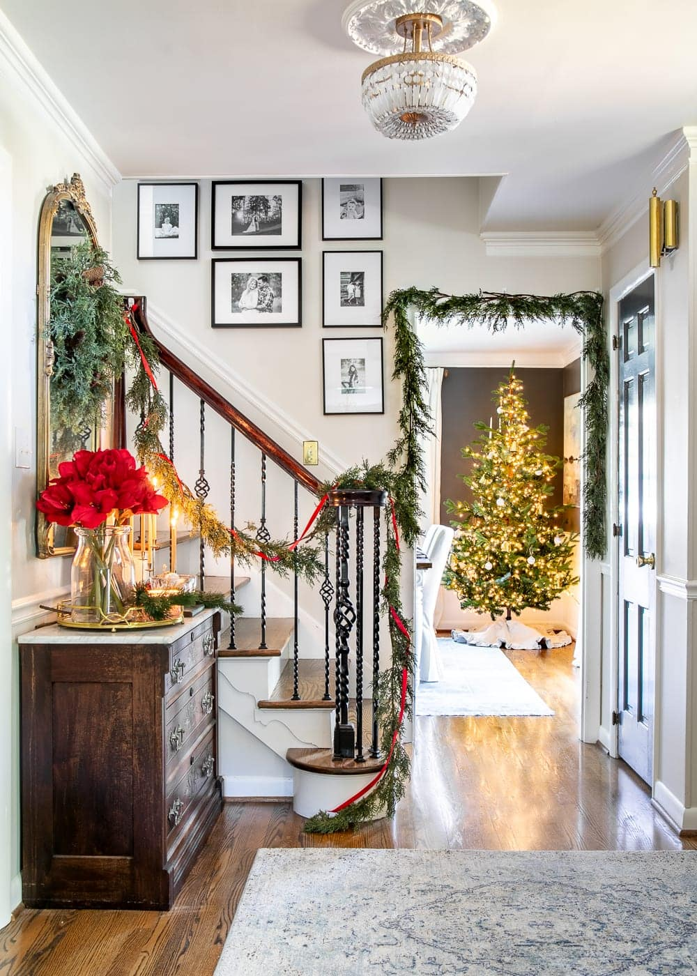 Christmas decor ideas | Modern meets traditional Christmas foyer with red amaryllis and real looking faux garland